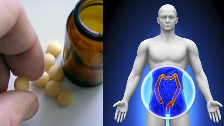 a hand holding a pill with several other pills on the table and a pill bottle and a body with an exposed colon