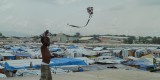 A child plays with a kite in a tent camp after the earthquake, Port-au-Prince, Haiti, 2010.