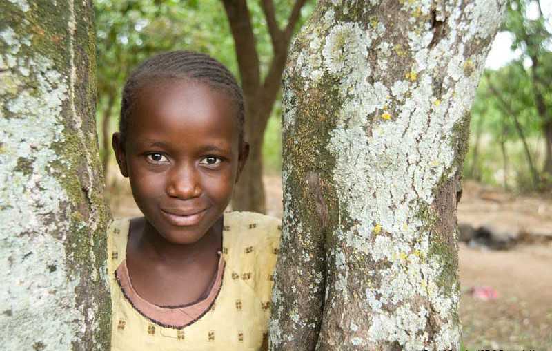 A girl leans against a tree in the village of Usoma, Kenya.