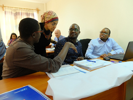 Oren (right) with some of his colleagues Dr. Vincent Yator (center) and Athanasio Omondi (left) engage with a International Union Against Tuberculosis and Lung Disease facilitator, Dr. Gihan El-Nehas (standing) during a group session.