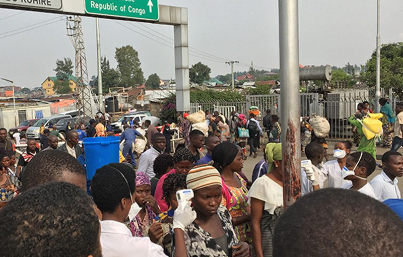Travelers get their temperature checked while crossing the DRC border into Rwanda.
