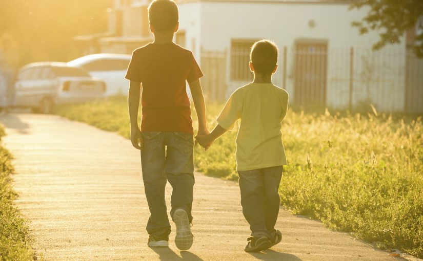 Two boys running together on street with sun back light, toned image