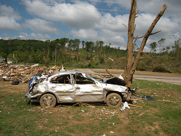 image of a car smashed into a tree, the result of tornado damage. Photo courtesy of the Georgia Emergency Management Agency