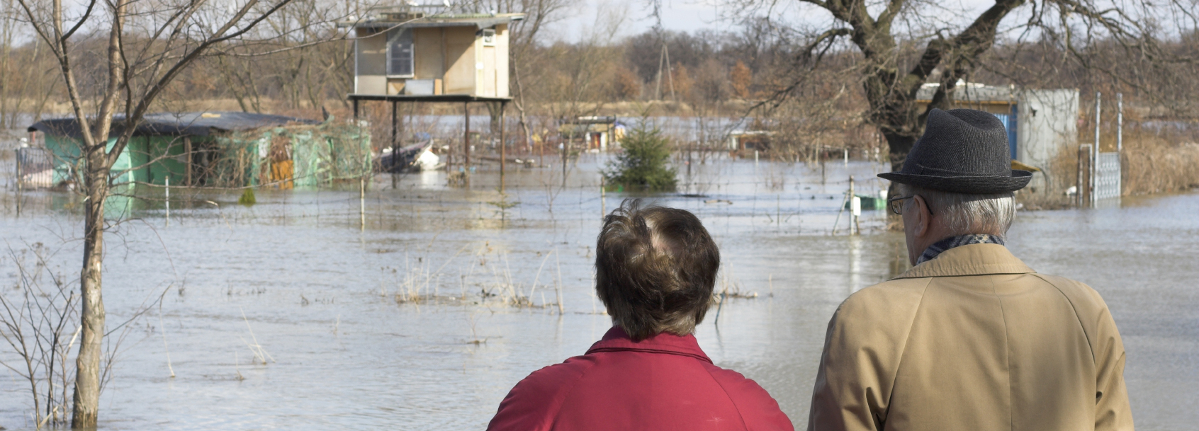 woman and man looking out over flooded houses and road