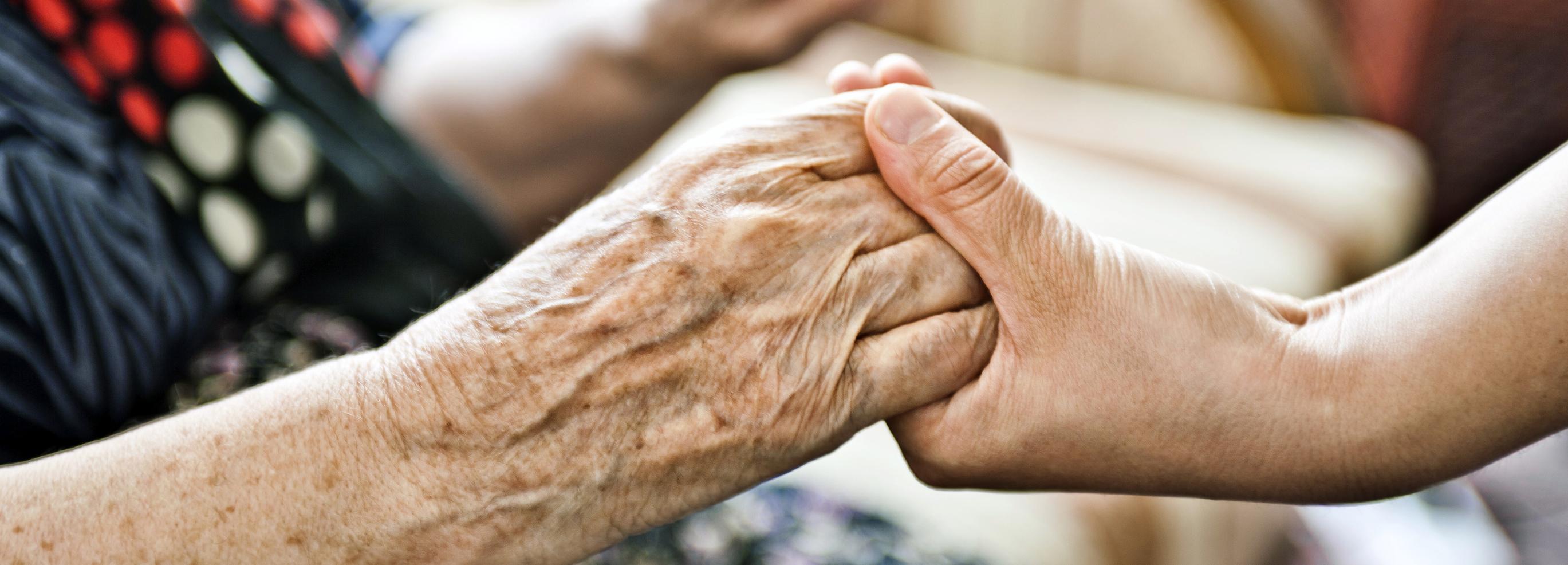 Younger adult holding older adult's hands