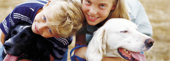 boy and girl each hugging a dog and smiling