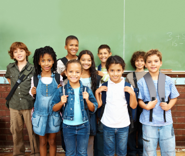 Children standing with backpacks on