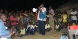 Community leader talking to villagers before a screening of the educational monkeypox video