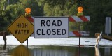 """Flooded road, with barrier and """"high water,"""" """"road closed"""" signs"""