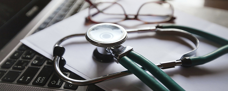 stethoscope on a piece of paper on top of a computer next to reading glasses