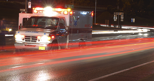 ambulance driving down the street at night