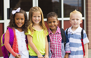 four children in front of school with bookbags