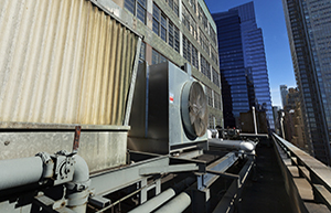 An outdoor HVAC air conditioner unit located on a high-floor porch of a midtown Manhattan skyscraper.