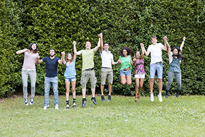group of young adults holding hands and jumping in the air