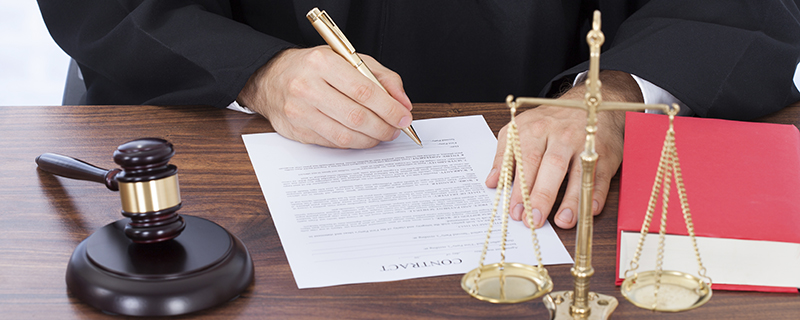Midsection of male judge signing contract paper at desk