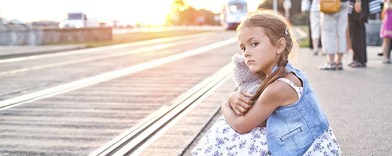 Small girl sitting on a tram platform with her toy teddy bear