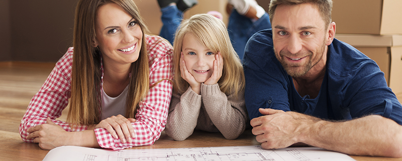 Mom, dad, and child with blueprints for house.