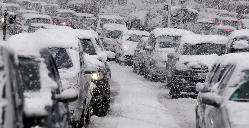 Cars driving on a highway are stuck in traffic because of a snow storm.