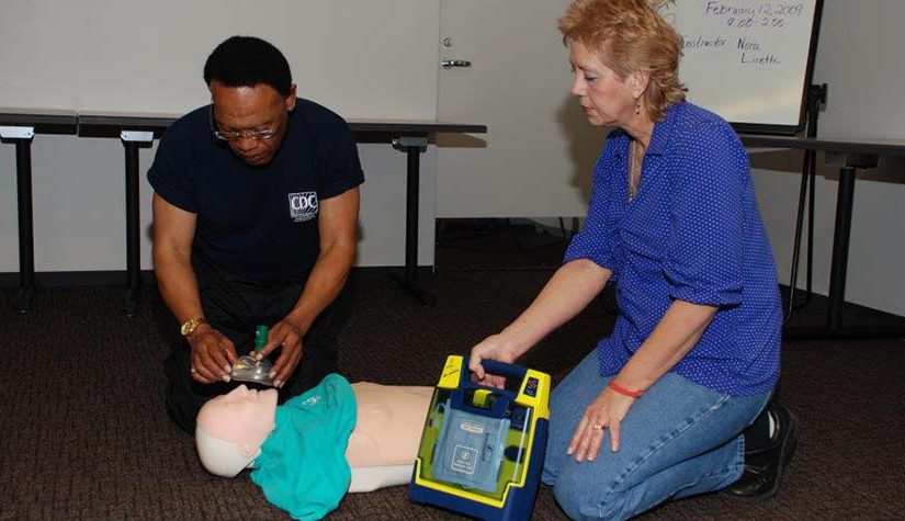Instructor and student practicing CPR on mannequin.