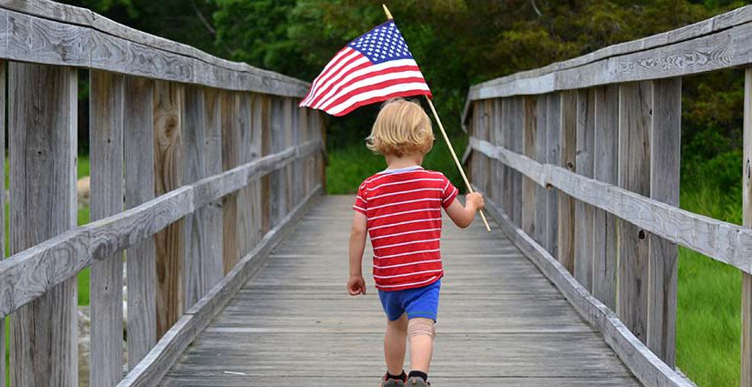 Young blonde boy carrying an American Flag over a wooden Bridge.