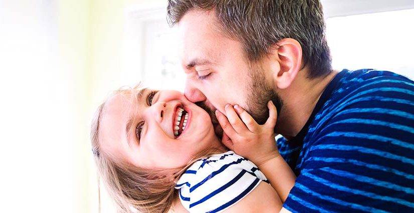 Close up of hipster father kissing his little daughter, sunny day