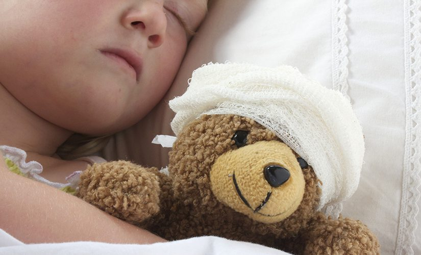 Girl in bed cuddling a teddy with bandage