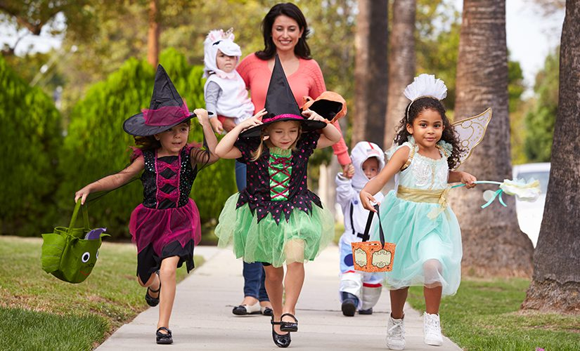 Parent taking children trick or treating at Halloween.