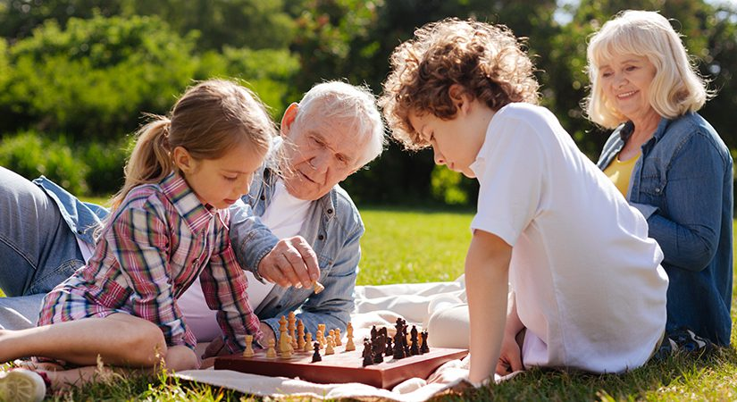 Children playing chess with grandparents