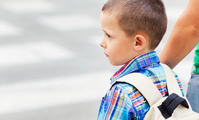 A boy and his mother wait to cross the street on their way to school.