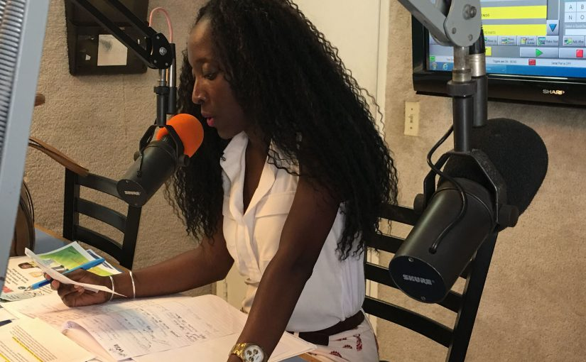 Nykole Tyson, Director of Public Relations for the US Virgin Islands Department of Health, speaking into a radio microphone.