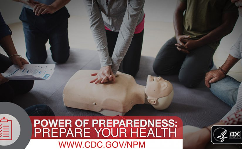 Group of people kneeling around a CPR dummy.