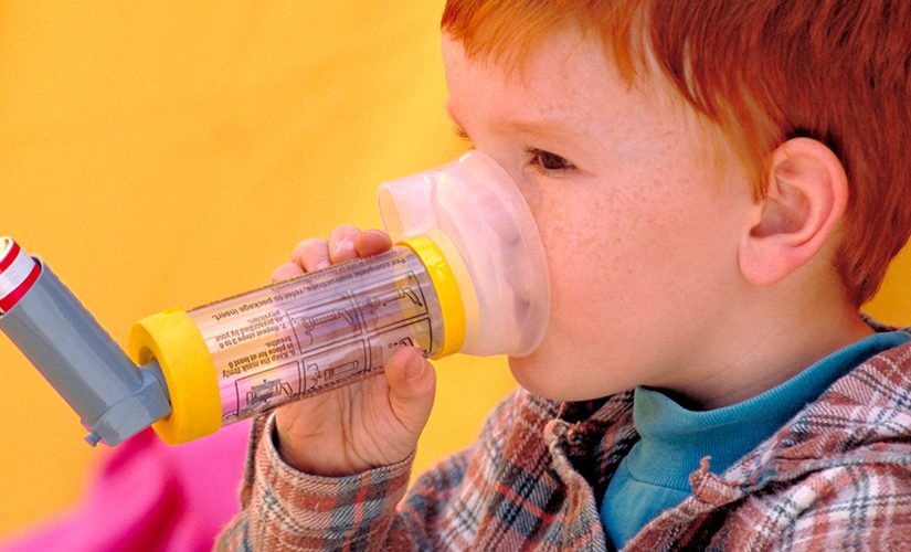 Little boy using a chamber to administer asthma medication