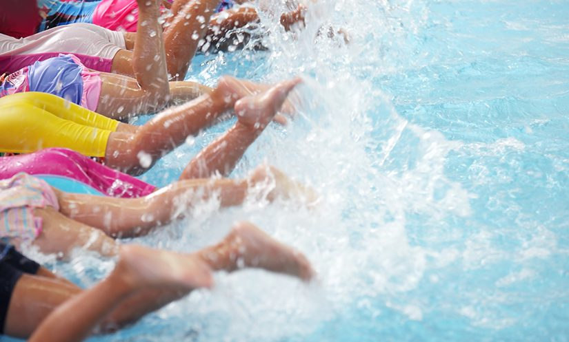 A group of children at a pool learning to swim.