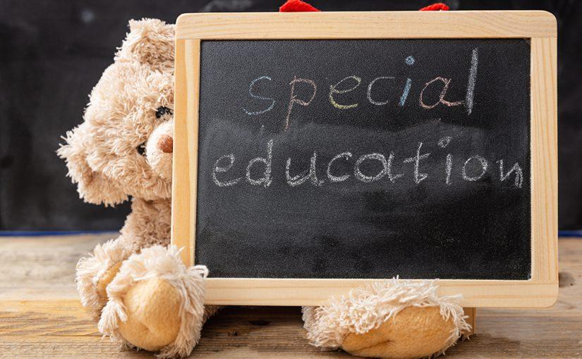 Special education. Teddy bear hiding behind a blackboard. Special education text drawing on the blackboard