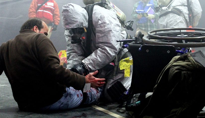 A first responder tends to a person with a simulated (or mock) injury during an emergency response exercise.