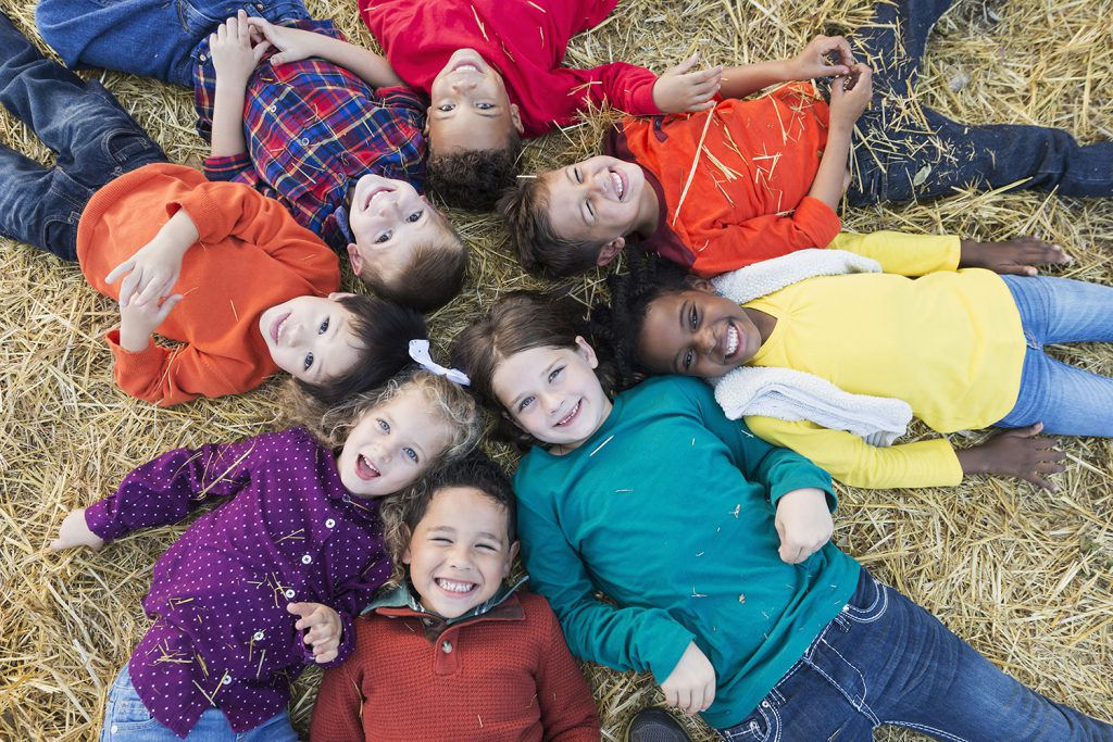 A group of eight multi-ethnic children, 4 to 6 years old, lying on their backs on hay, in a circle with heads in the middle, smiling at the camera.