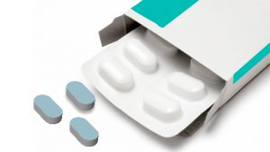 a blister pack of tablets and thee blue tablets out on the table
