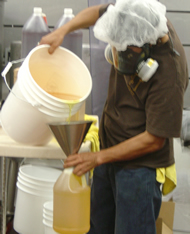Worker pouring flavoring chemicals
