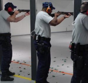 three men aiming guns in a firing range