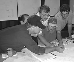 several men pointing at papers on a table