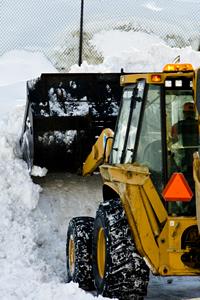 Heavy equipment shoveling heavy snow