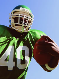 A football player in a green jersey holding a football.