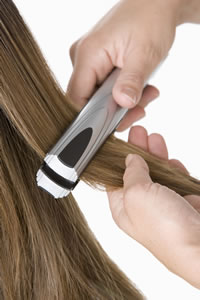 photo of a woman's hair being straightened
