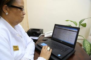The director of a clinic reviews patient data on hypertension control rates in Matanzas, Cuba.