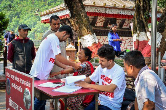 May Measurement Month volunteers screen local resident outside of a temple in Pokhara, Nepal. Photo credit: Kiran Adhikari