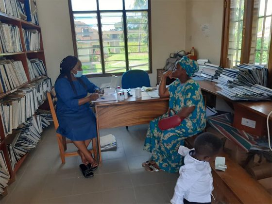 Redempta Mushi, Amref-supported-Pediatric officer, Afya Kamilifu attending to a client in a de-congested environment.