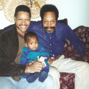 Photo of Demetrius Parker in 1996 holding his young son Vitthal, and seated next to his late father John H. Parker, Sr.