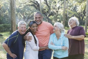 A group of five multi-ethnic seniors standing together in a park wearing casual clothing. The African-American couple in the middle are smiling and the others are laughing.