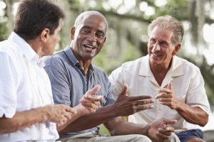 A diverse group of older men sitting outdoors, having a conversation