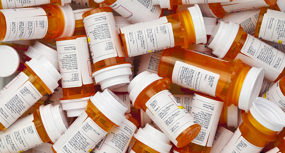 A jumble of orange prescription pill bottles with white labels and lids.
